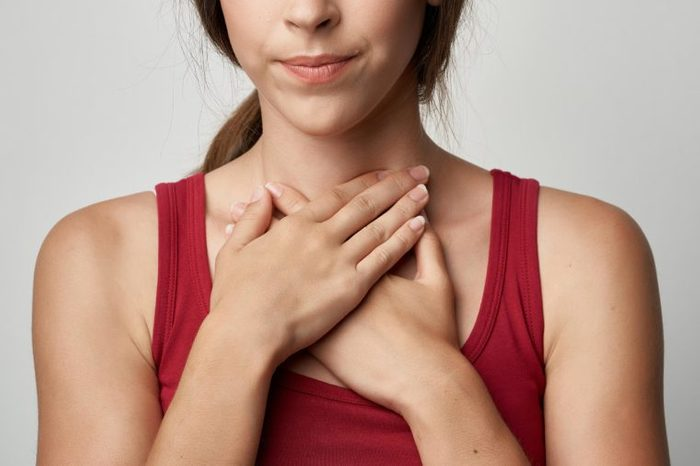 woman holding both hands to her throat