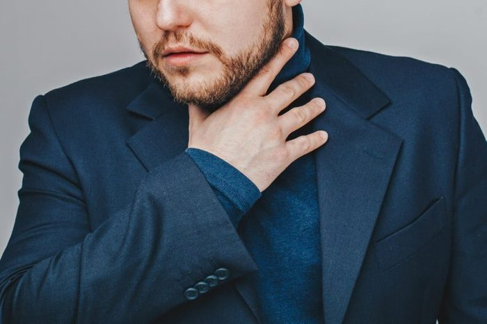 man in blue suit holding throat