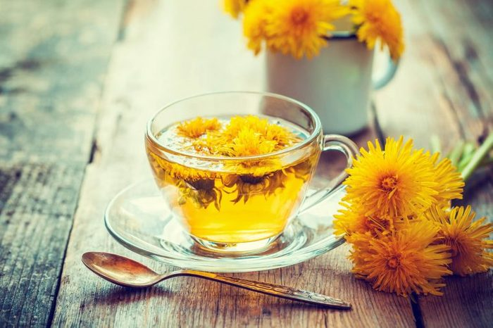glass mug of elecampane flower tear, next to flowers