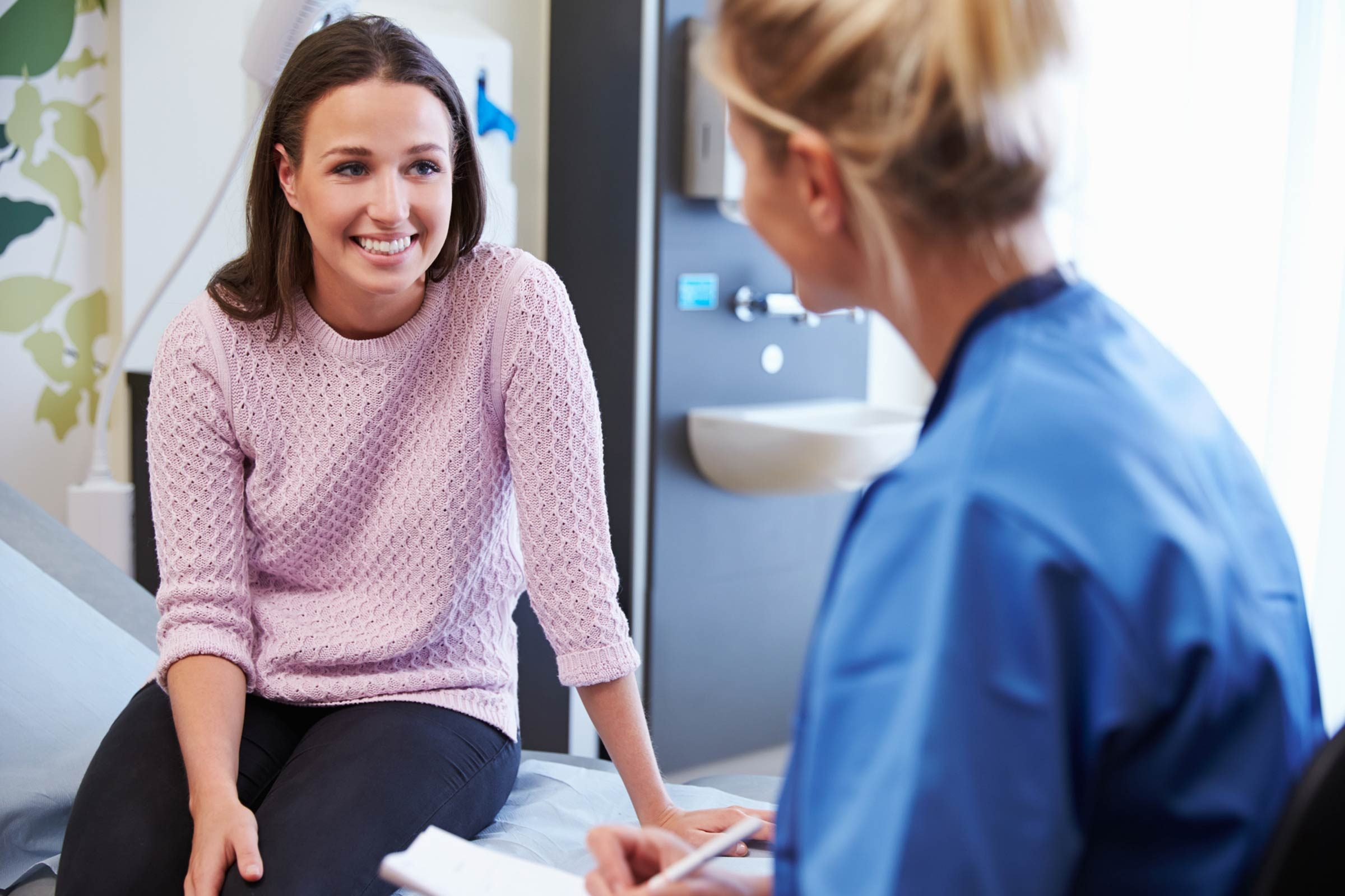 Smiling woman talking to doctor in office.