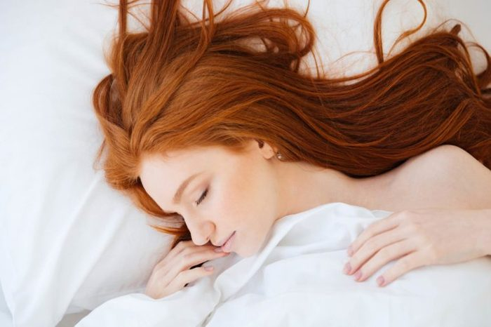red-haired woman asleep in bed