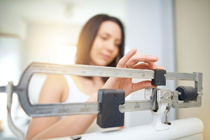 woman weighing self on scale