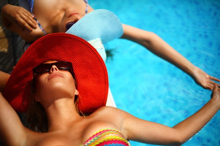 woman in red hat and sunglasses next to pool