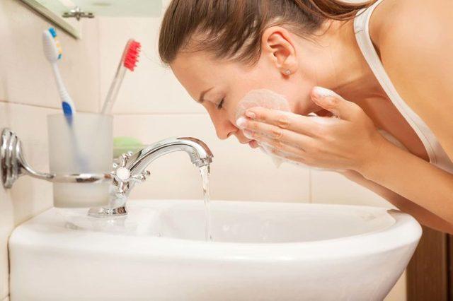 woman washing face at white sink