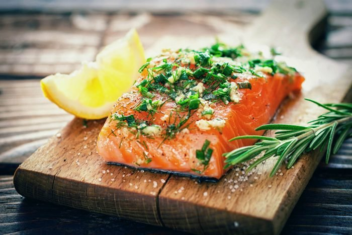 salmon steak with herbs and lemon on a wooden cutting board