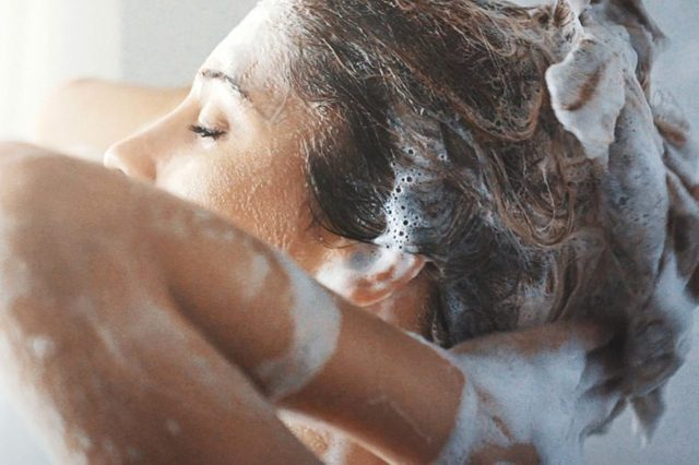 woman rinsing shampoo from hair