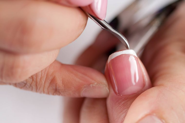 shaping nails with a manicurist's tool