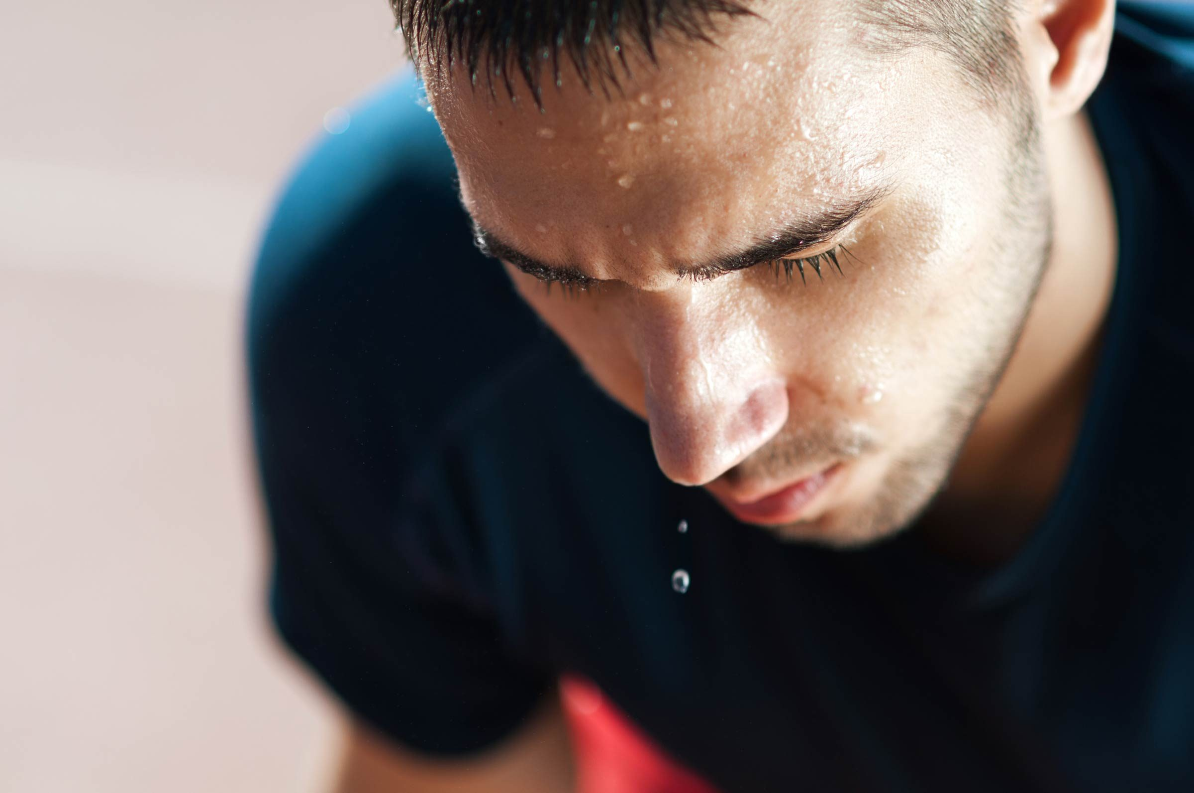 Man's face drenched in sweat
