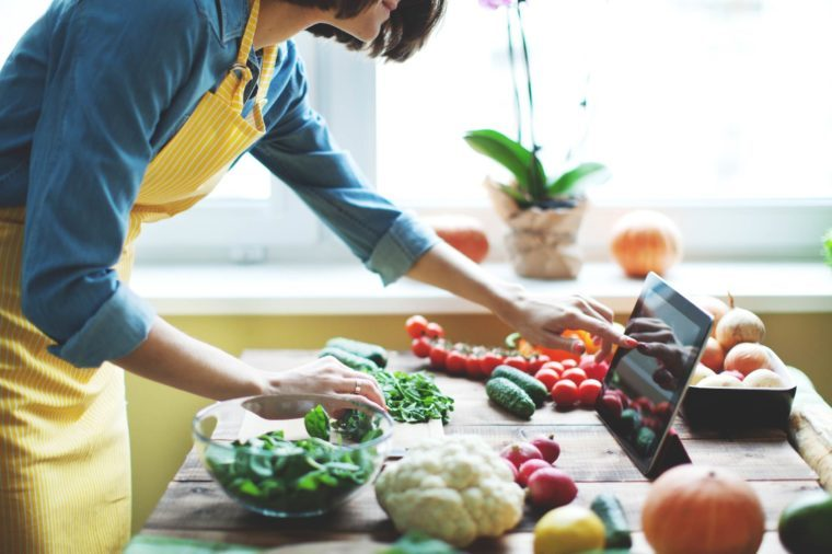 woman with apron cooking with veggies on a wooden counter, checking an iPad