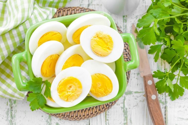 halves of boiled, peeled eggs in a green dish