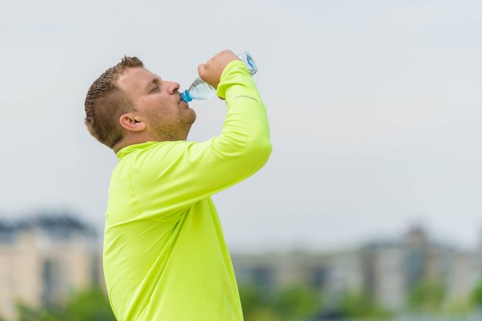 man in a yellow long-sleeve shirt drinking from a water bottle