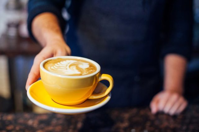 barista serving coffee in yellow cup