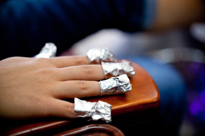 hand with nails wrapped in foil