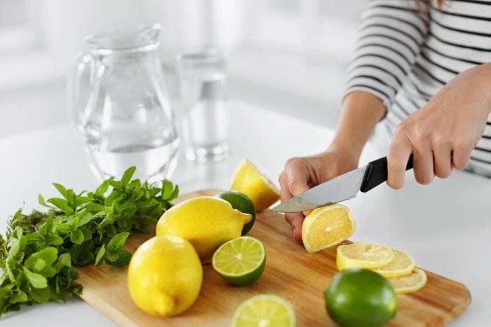 woman cutting lemons and limes