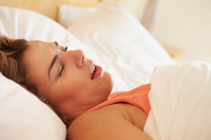 woman on her back, asleep in bed, snoring with mouth open