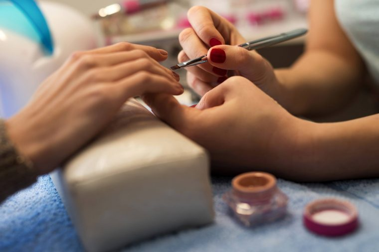 close up of a manicurist working on a customer's nails