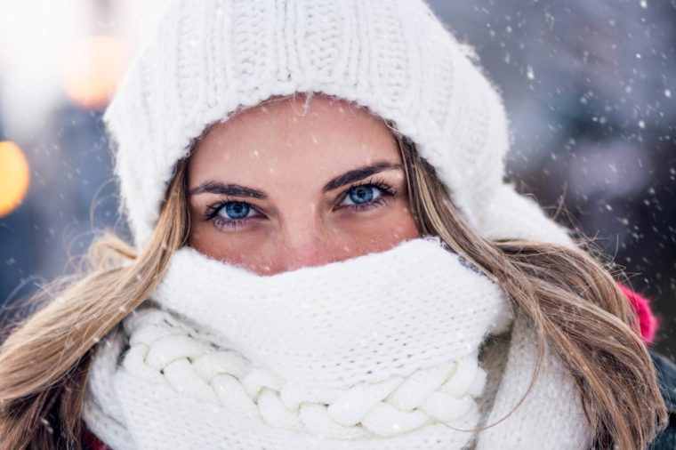 woman with blue eyes outdoors, bundled up in white hat and scarf
