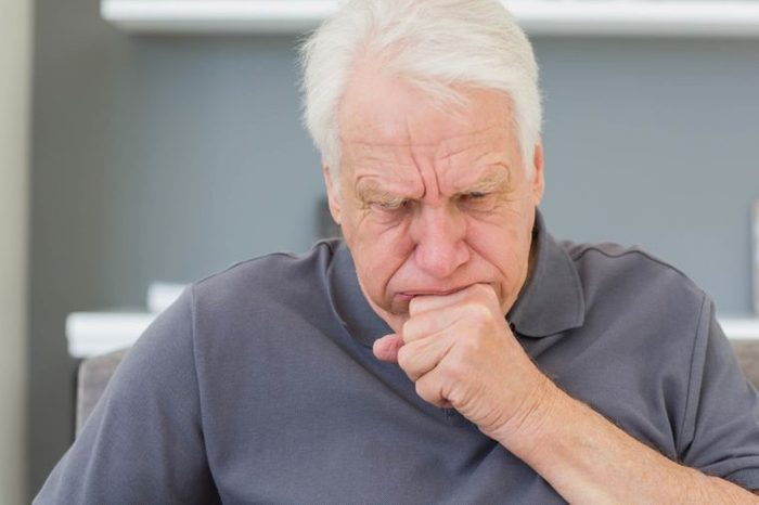 elderly man coughing into his hand