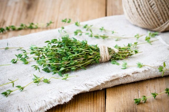 sprig of thyme on a dish towel tied with twine