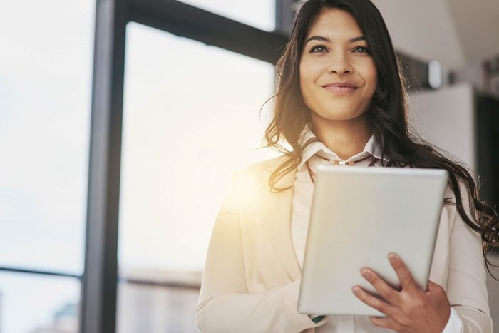 Smiling woman holding computer tablet.