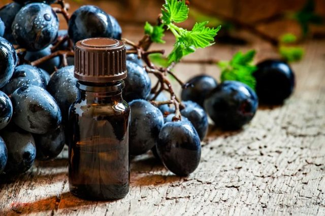 brown vial on wood table with grapes behind it
