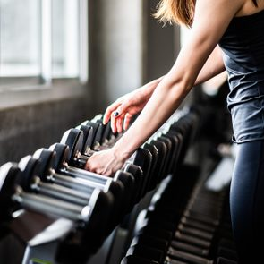woman picking up weights in the gym
