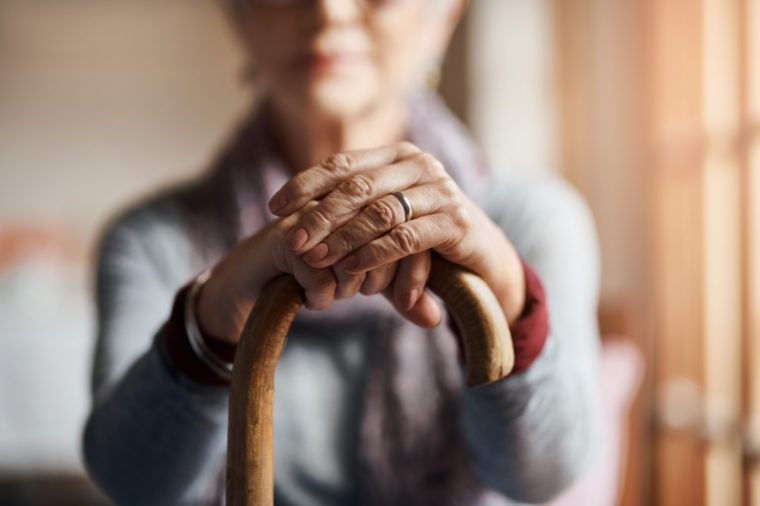 senior woman holding a cane in a retirement home elderly