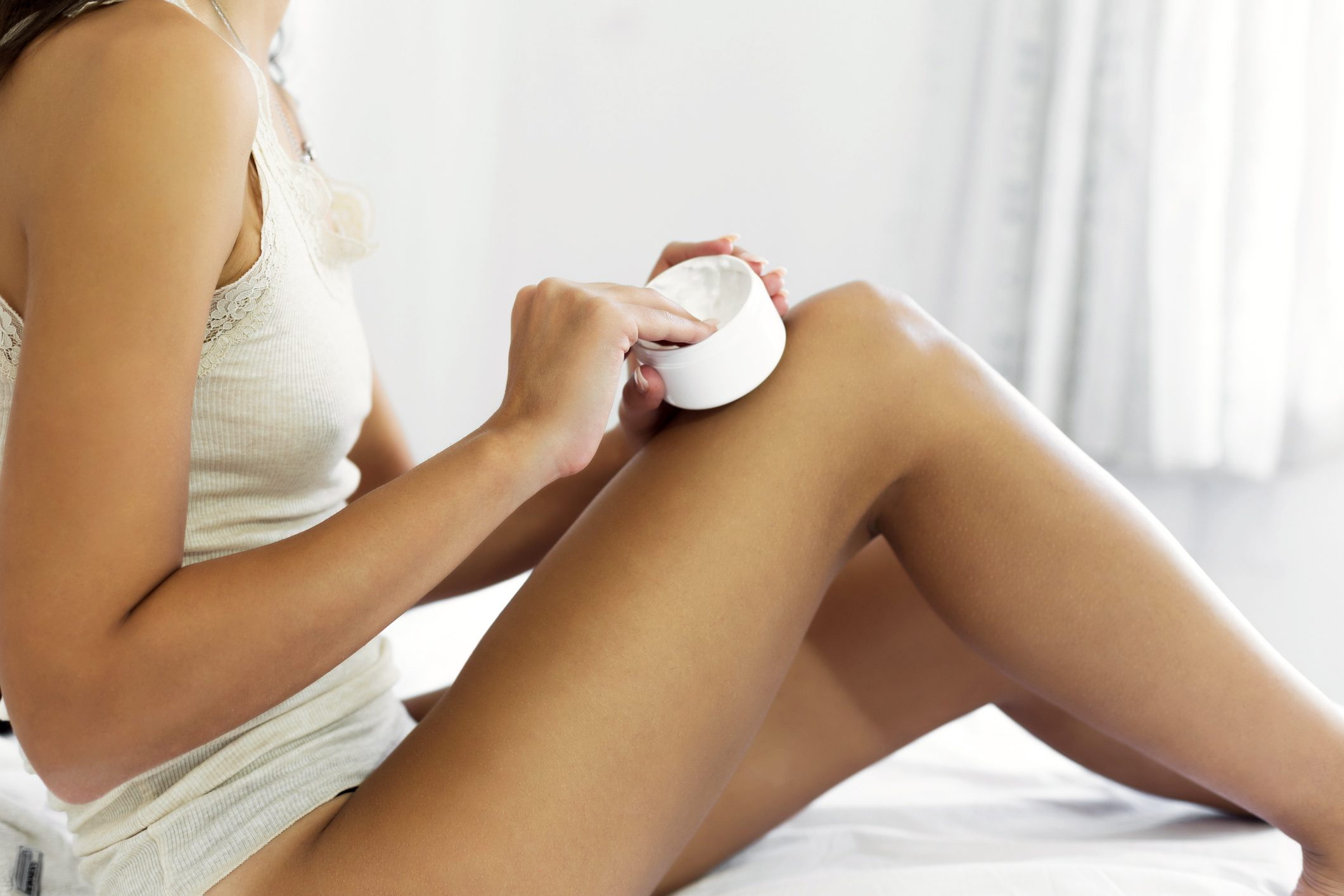 woman applying moisturizer to legs
