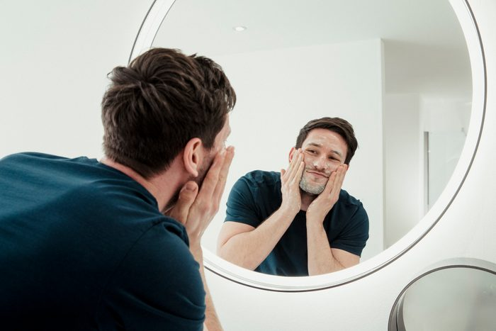 man washing face while looking in the mirror
