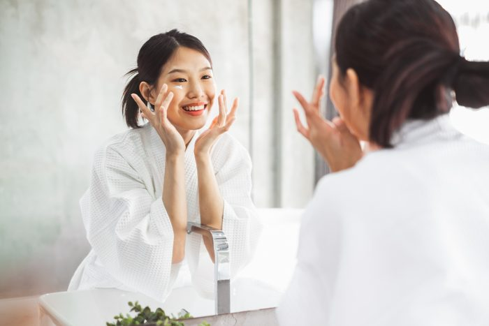 woman moisturizing face while looking in mirror