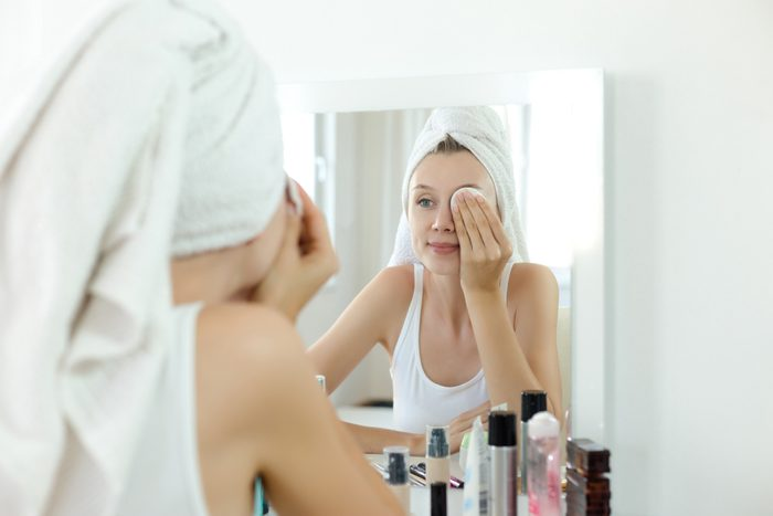 young woman cleaning her face in mirror