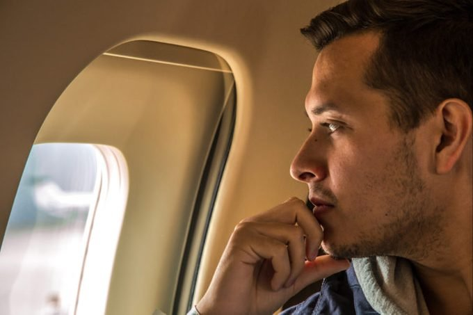 man looking out airplane window