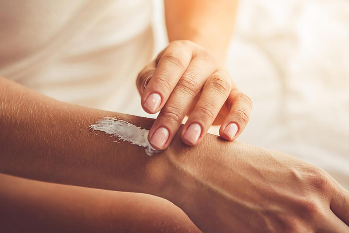 rubbing skin product on arm