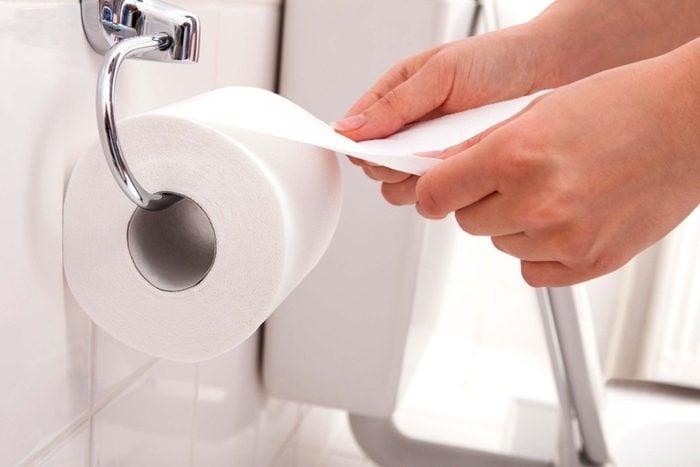 person grabbing toilet paper
