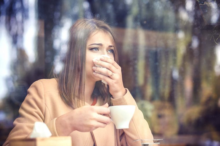 woman looking through a window holding a tissue to her nose