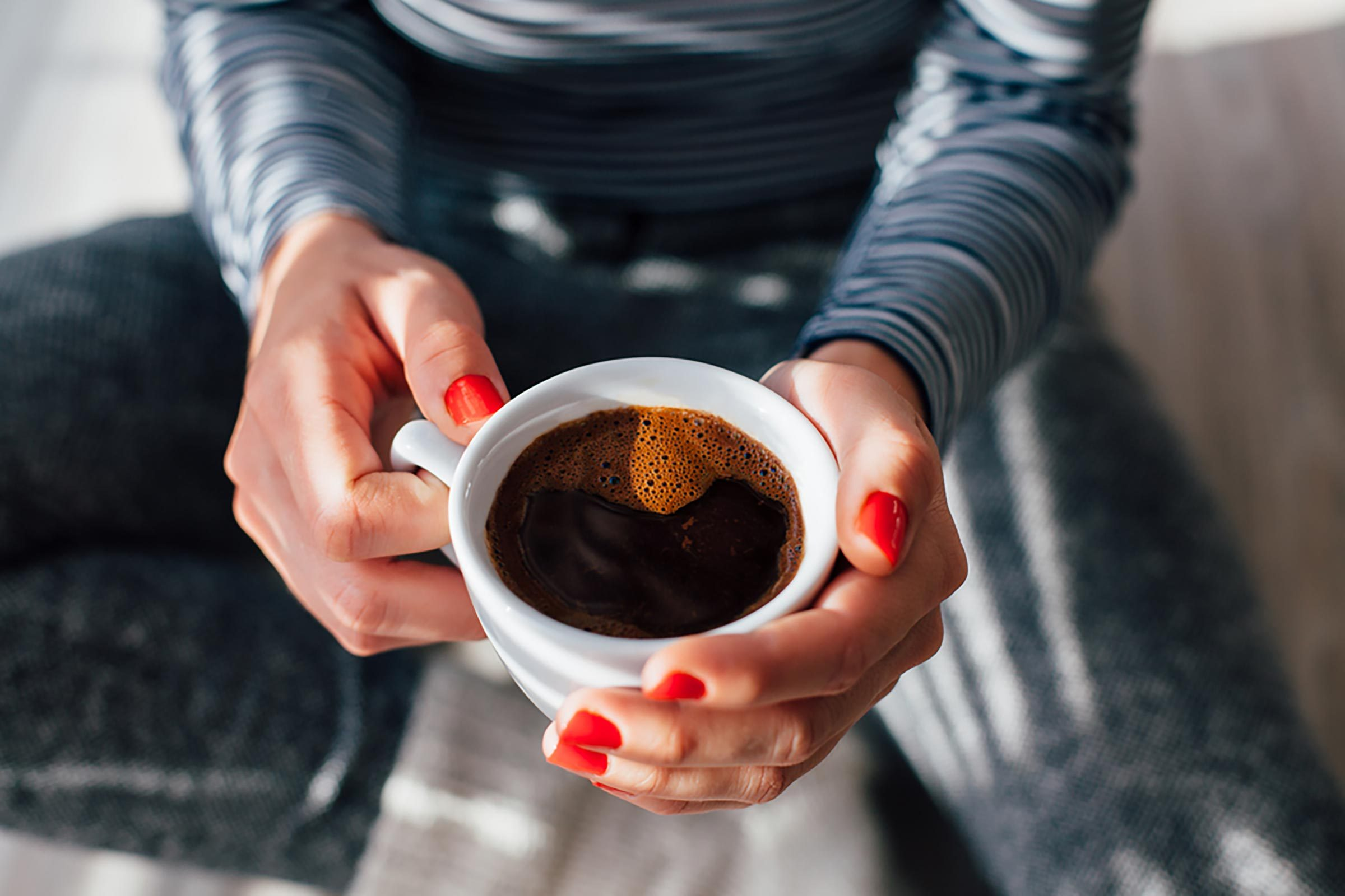 woman's hands, holding cup of coffee