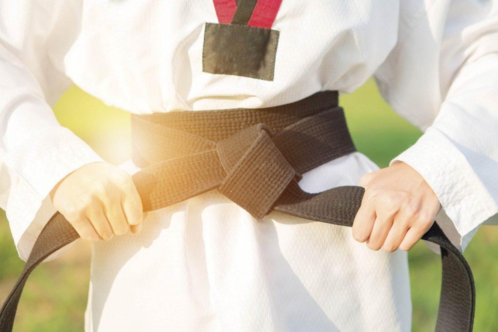 person tying on karate belt