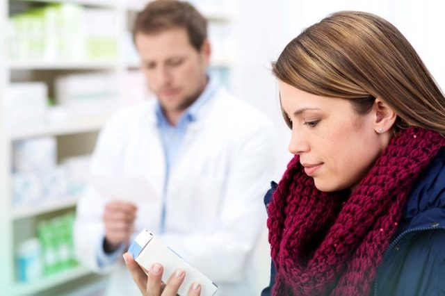patient looking at Rx in pharmacy with pharmacist in background