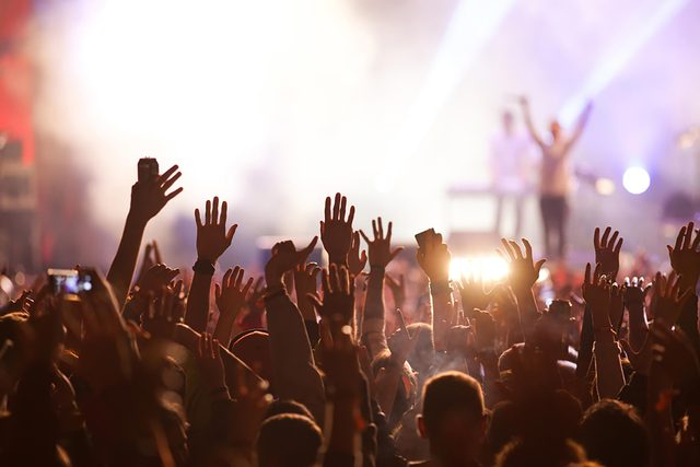 concert with fans waving hands