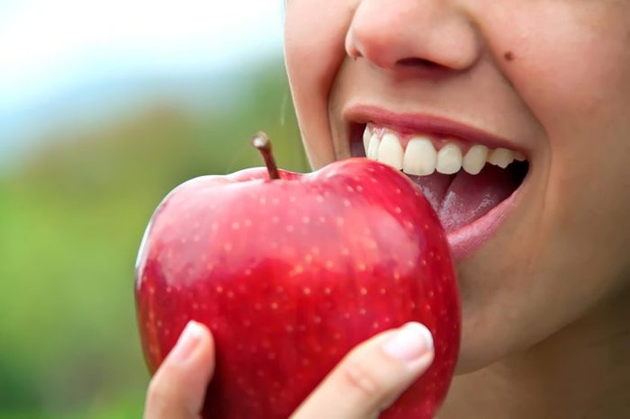 a woman taking a bit out of an apple