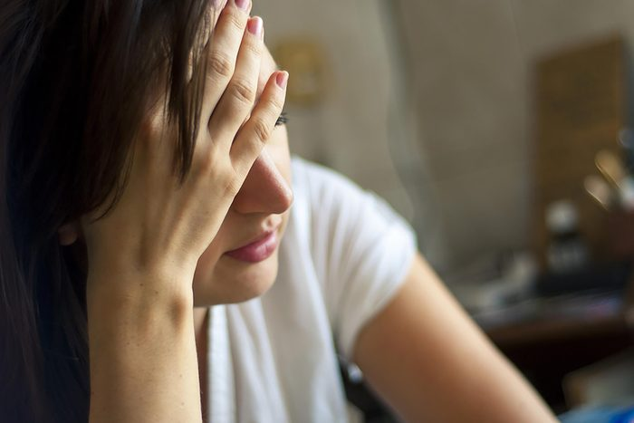woman holding forehead looking stressed