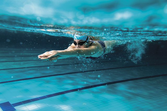 person underwater swimming in pool