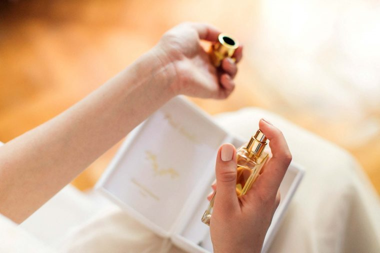 closeup of woman's hands spraying perfume on her wrist