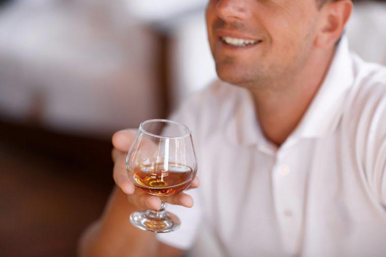 man holding glass of brandy