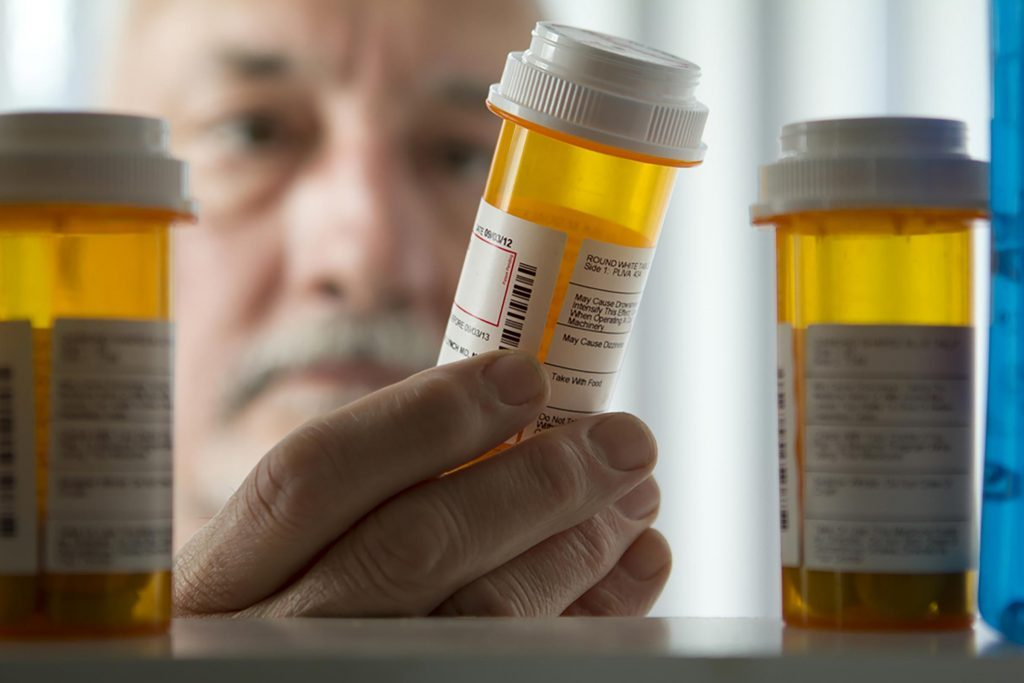 man looking at prescriptions in bottles