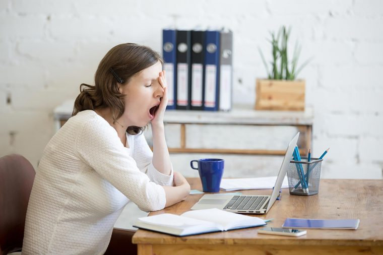 woman sitting at desk in front of computer yawning