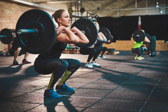 Woman in gym lifting heavy weights