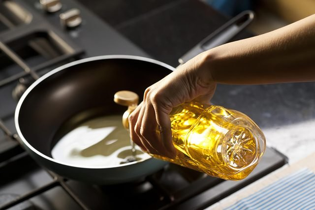 woman pouring olive oil in a skillet on a stove