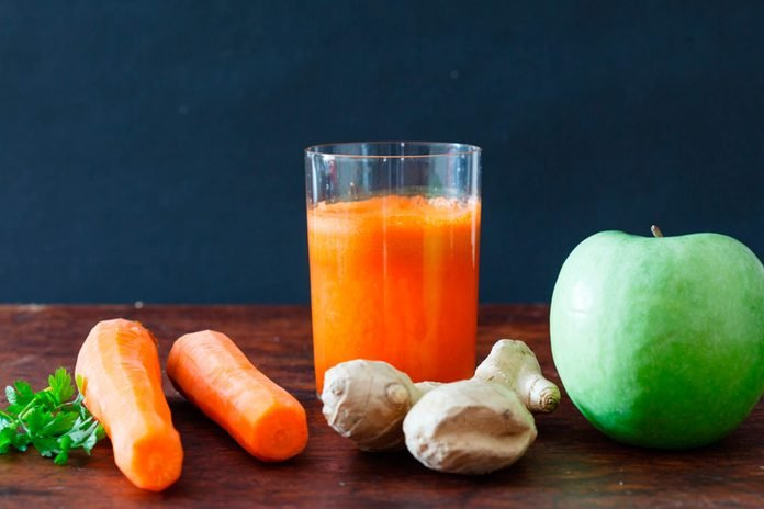 glass of carrot juice with carrots, ginger, apple, and parsley