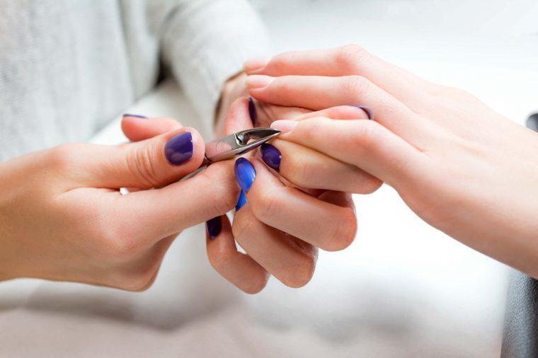 manicurist cutting cuticles